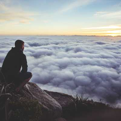 Unsplash Man on mountain looking over clouds
